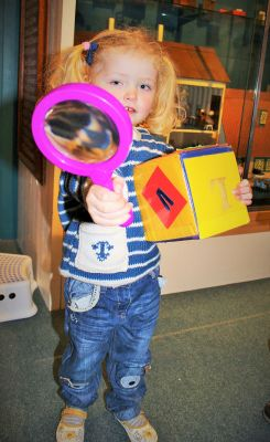 A girl holding a magnifying glass and a giant die