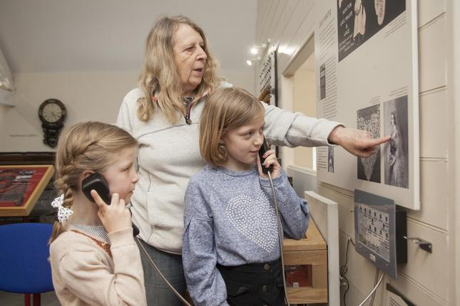 Two girls holding wired telephone handsets to their ears with a woman standing behind them