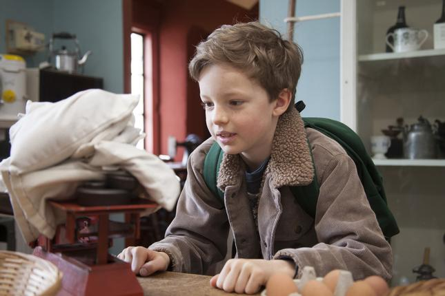 A boy sitting at a table looking at some scales