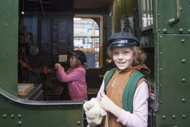 Two girls wearing engine driver caps in the cab of a steam engine