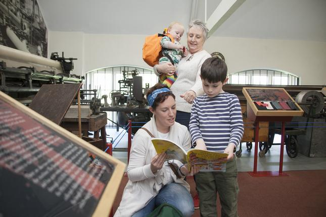 Two women, a boy and a baby looking at a book