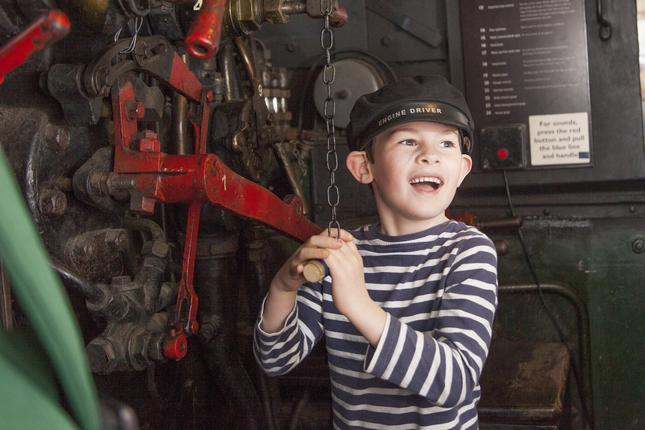 A boy standing in the cab of a steam engine