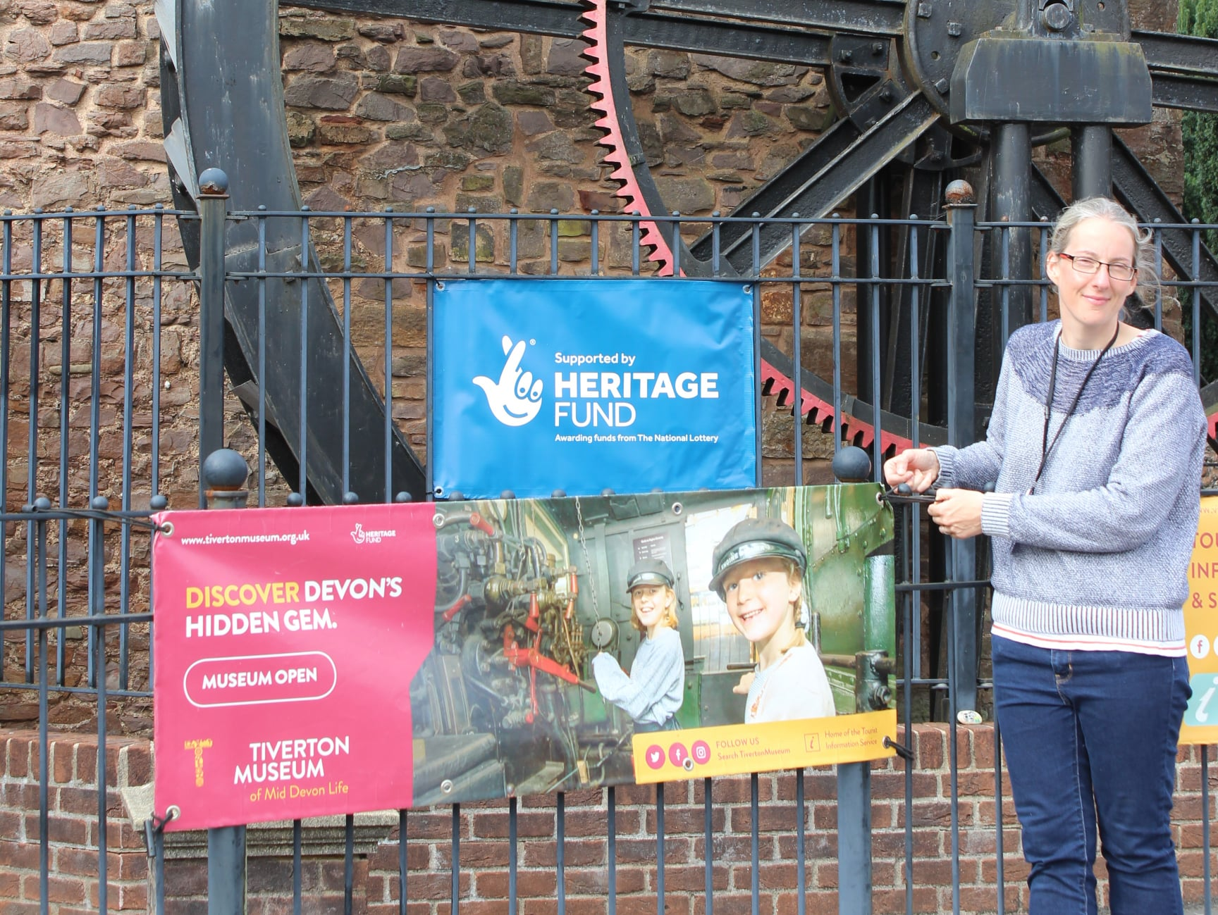 Museum Director putting open banner outside museum for the first time in nearly 6 months
