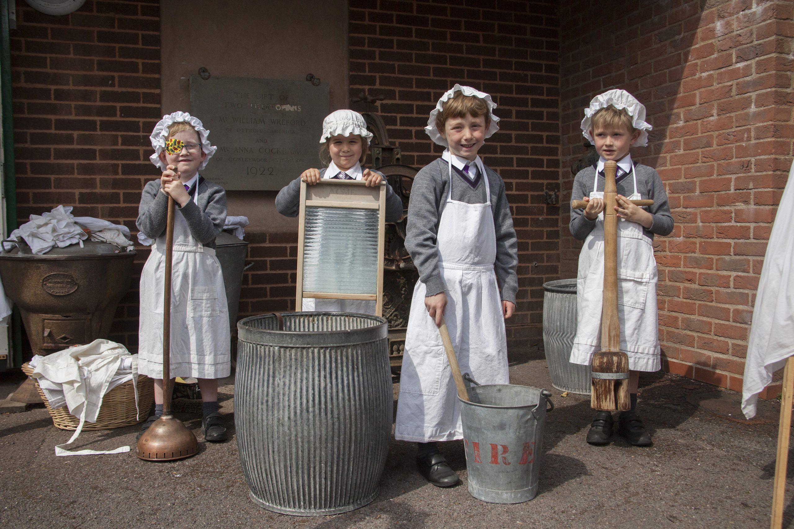School children posing with Victorian laundry equipment