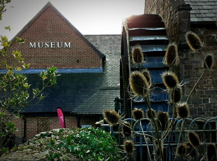 The exterior of the museum building with a watewheel and teasels in the foreground