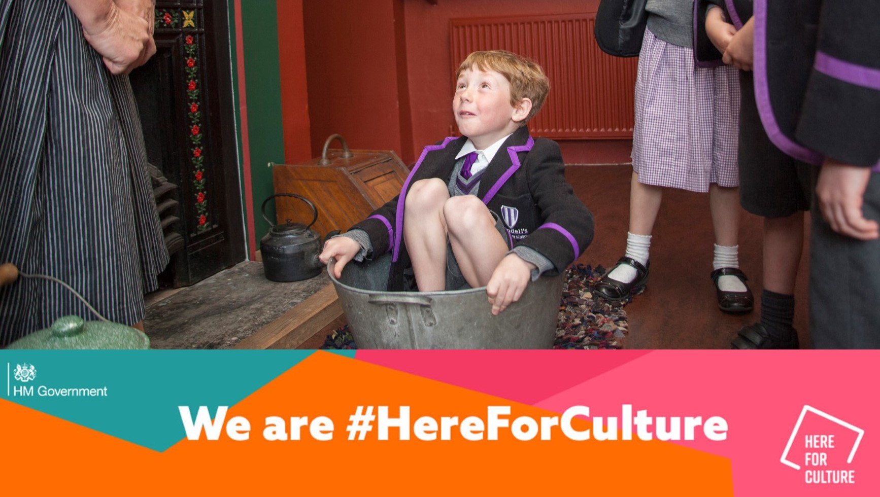 Boy in school uniform sits in a tin bath with the caption We are here for culture
