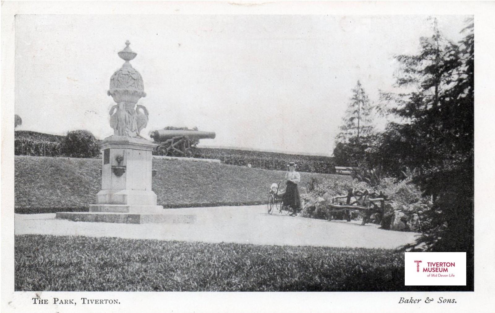 A large ornamental drinking fountain in a park with people in Edwardian dress.