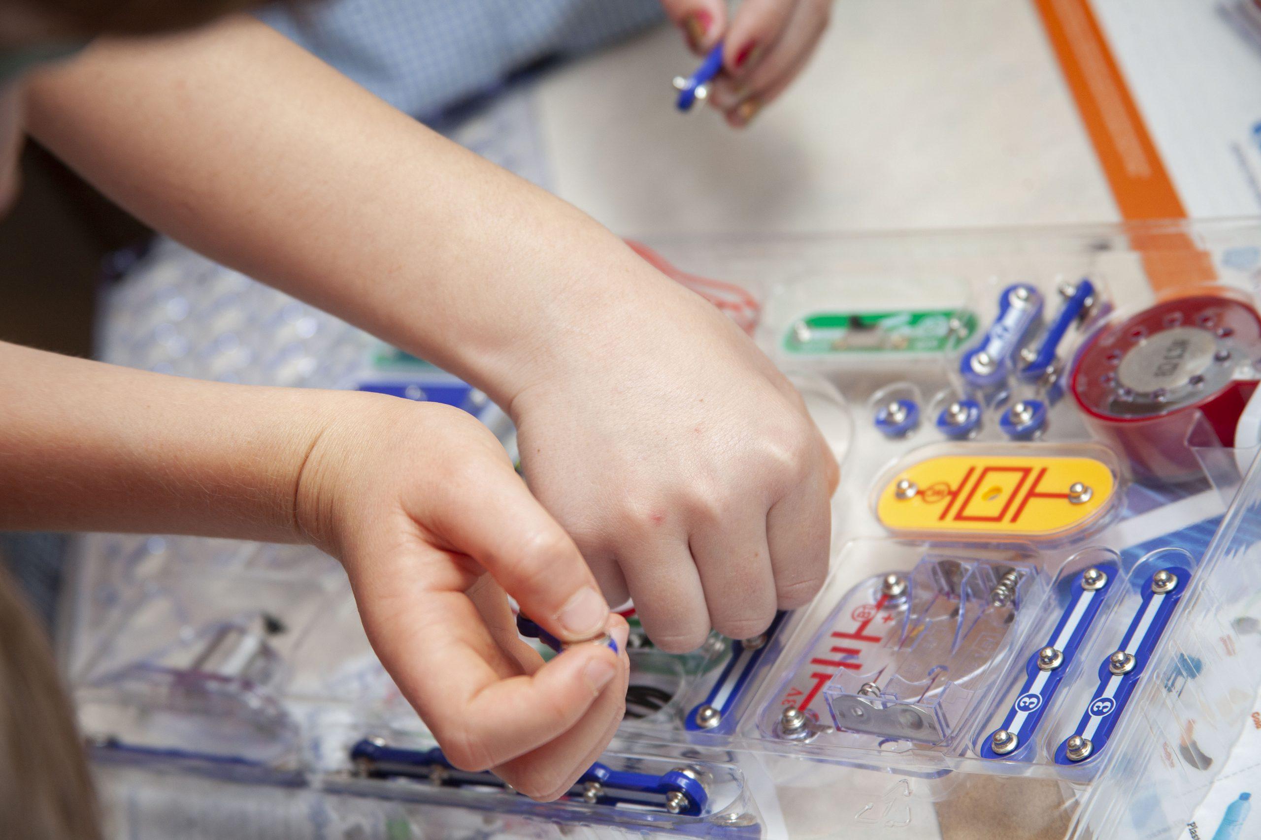 Children's hands above a circuit board