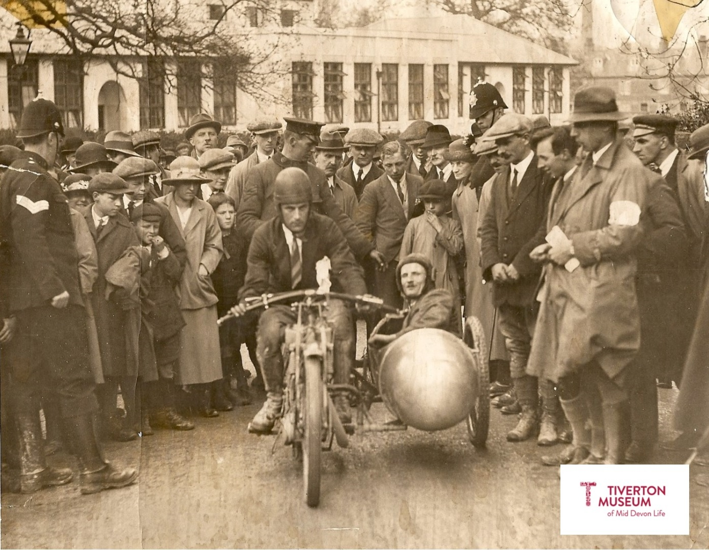 An old fashioned motorbike and sidecar with a crowd of people