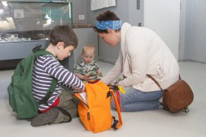 A family sitting on the floor of a museum gallery, looking into a backpack